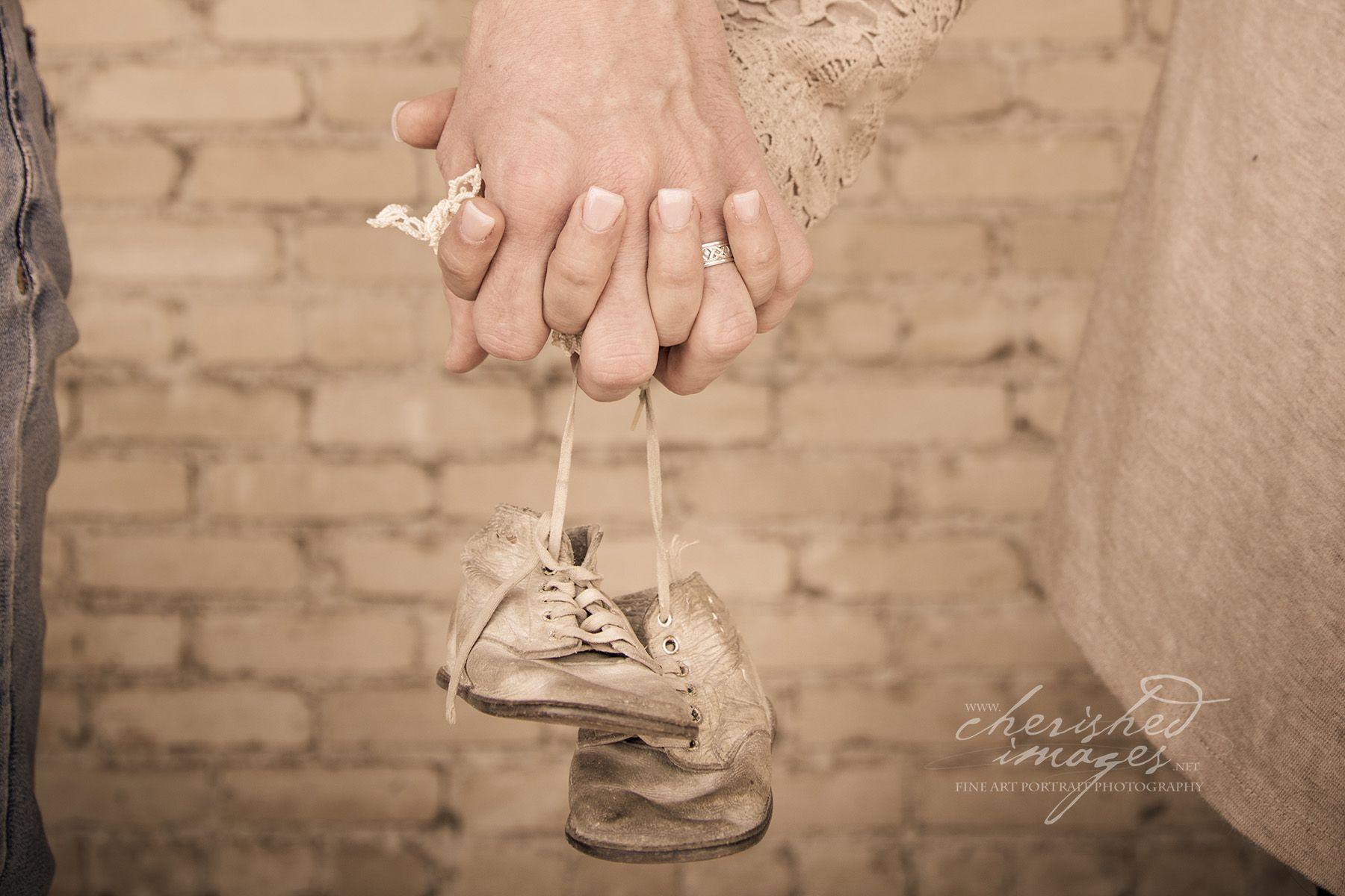Cherished Images Newborn Baby Photographer photographs couple holding baby shoes