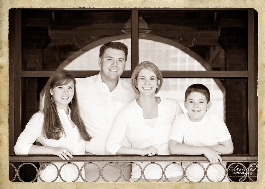 family portrait in front of arched window